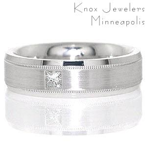 Atlanta is a sophisticated band shown in 14k white gold. A 0.15 carat princess cut diamond is flush set in the middle of the band for appeal. The beveled band is detailed with three textures: high-polished beveled sides, a matte finished middle, and two grooves that have a reversed milgrain texture.