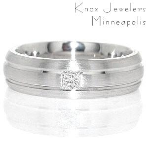 Knox Jeweler's Miami is a unique contemporary gent's band featured in 14k white gold. Two grooves evenly spaced, run parallel along the design in a high polish finish. The raised surface is given a matte finish, giving depth to the channels. A 0.15 carat princess cut is fashioned in center of the band for interest.