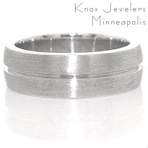 The Jersey band is a prominent design crafted in 14k white gold. The wide presence of the band slightly domes for a well suited fit. A single channel is forged down the band center. The brushed finish to the surface highlights the eternity channel stripe.