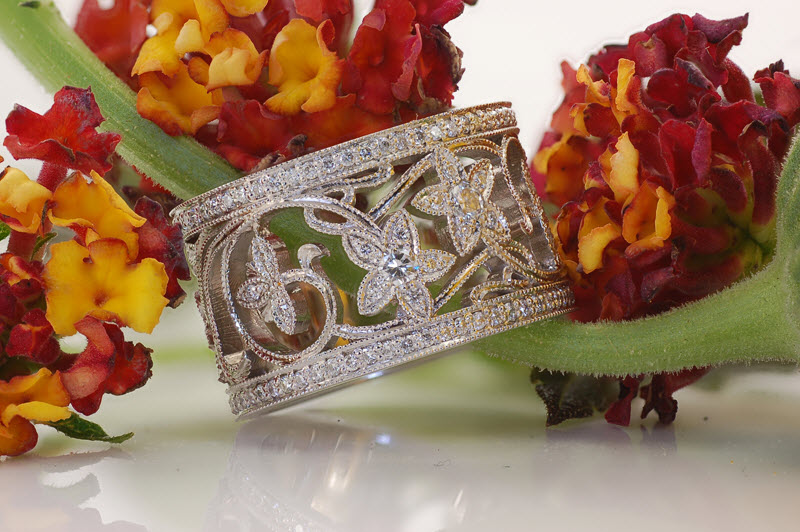 Custom wide band engagement ring with a bead set diamond floral pattern.